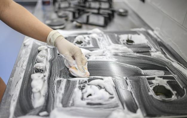 Reinigingsmiddel schuim op een gasfornuis de keuken schoonmaken