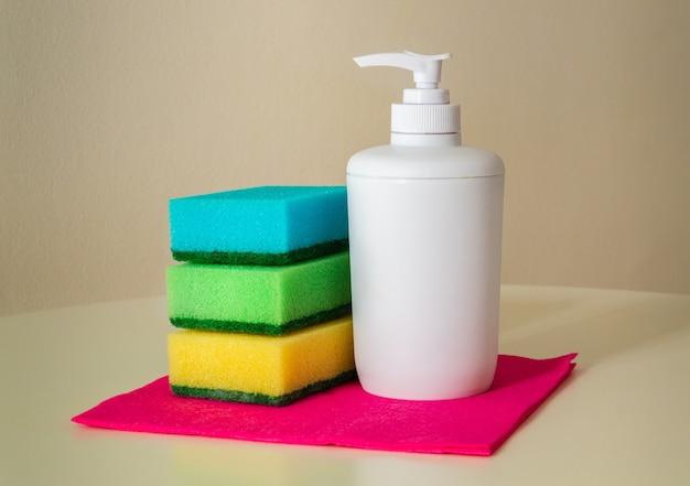 Reinigingsproduct shampoo en washandjes op rode doekjes voor afstoffen. de stofzuiger zorgt voor hygiëne in huis