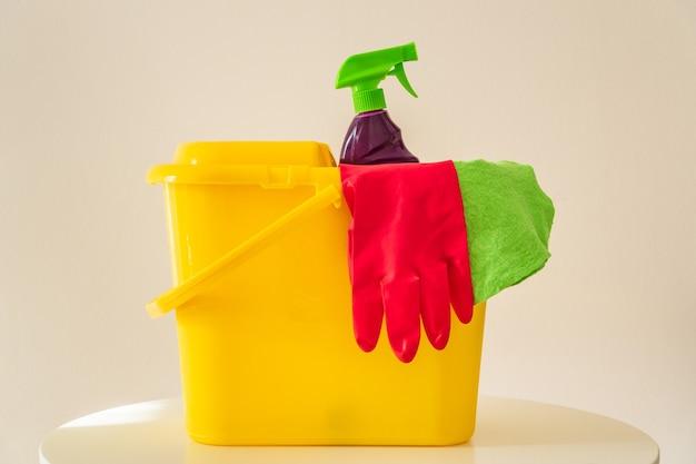 Reinigingsproducten shampoo en rode handschoenen in gele emmer. de reiniger zorgt voor hygiëne in huis