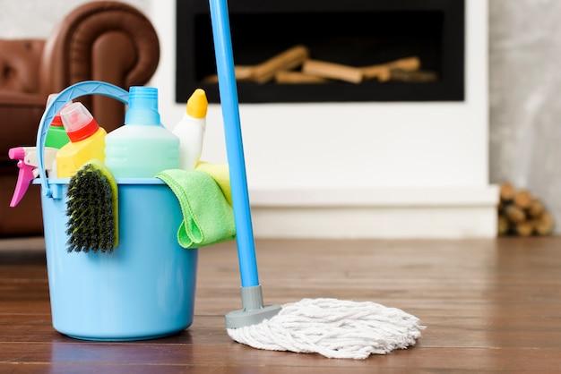 Reinigingsset en producten in blauwe emmer met zwabber