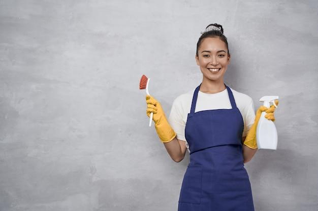 Reinigingsset. portret van een jonge gelukkige vrouw, mooie schoonmaakster in uniform met schoonmaakborstel en spray, glimlachend in de camera terwijl ze tegen een grijze muur staat. huishoudelijk en huishoudelijk werkconcept