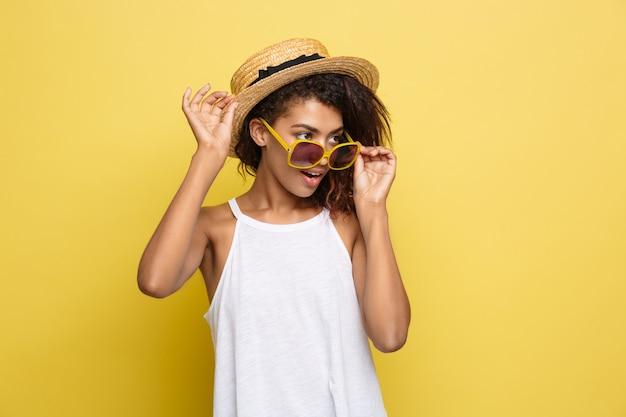 Reis concept - close-up portret jonge mooie aantrekkelijke afrikaanse amerikaanse vrouw met trendy hoed lachend en blije uitdrukking. gele pastelstudio achtergrond. kopieer de ruimte.