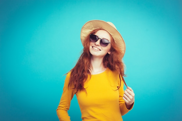 Reis concept - close-up portret jonge mooie aantrekkelijke roodharige meisje wtih trendy hoed en zonnebril lachend. blauwe pastelachtergrond. kopieer de ruimte.