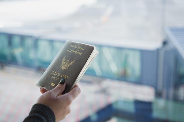Reis concept. close-up van vrouwenhand die thais paspoort klaar aan het inschepen houden.