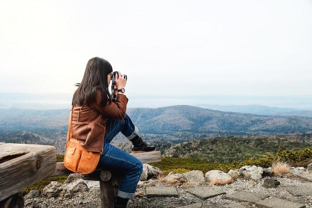 Reis concept. jonge reizende vrouw met camera foto te nemen in de herfst