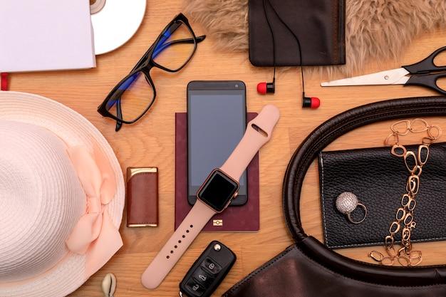 Reis concept. sleutel, hoofdtelefoon, paspoort, hoed, zonnebril, horloge en tas op hout