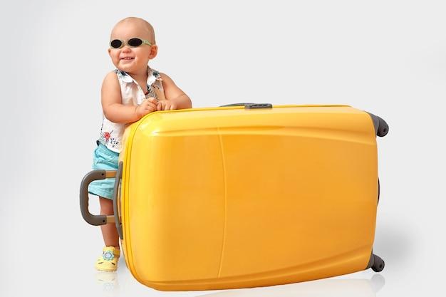 Reis concept. todler met een grote gele koffer.