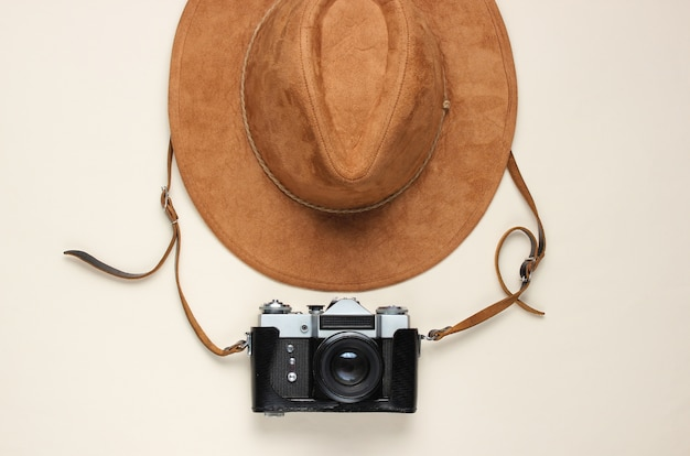 Reis concept. vilten hoed en film retro camera op beige, plat leggen