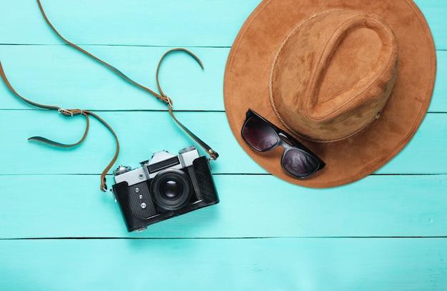 Reis concept. vilten hoed en film retro camera op blauw hout. plat leggen. bovenaanzicht