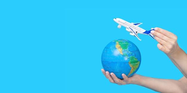 Reis concept. vrouwelijke handen met globe en beeldje van passagiersvliegtuig op blauwe achtergrond. het vliegtuig vliegt naar de wereld.