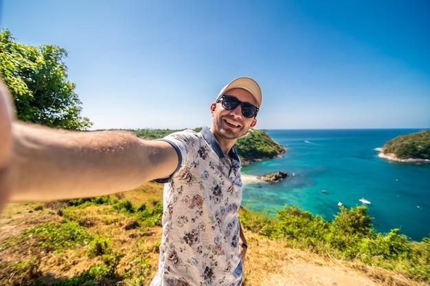 Reis de jonge mens status neemt een foto met smartphone en ziet mooie de aardmening van het landschapslandschap op rotsberg in phuket thailand.