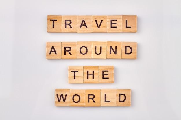 Reis de wereld rond. inspirerende quote gemaakt met houten letterblokken op witte achtergrond.