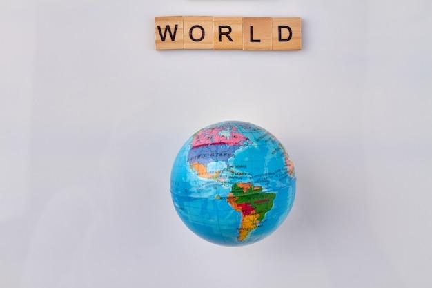 Reis de wereld rond. wereldconcept gemaakt van houten letterblokken. globe op witte achtergrond.