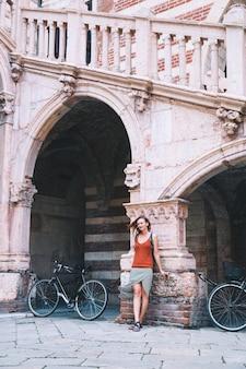 Reis door europa. jonge stijlvolle vrouw op de achtergrond van european city street en een van de historische architectonische gebouwen van verona, italië. vakantie in europa. kunst, lifestyle en reisconcept.