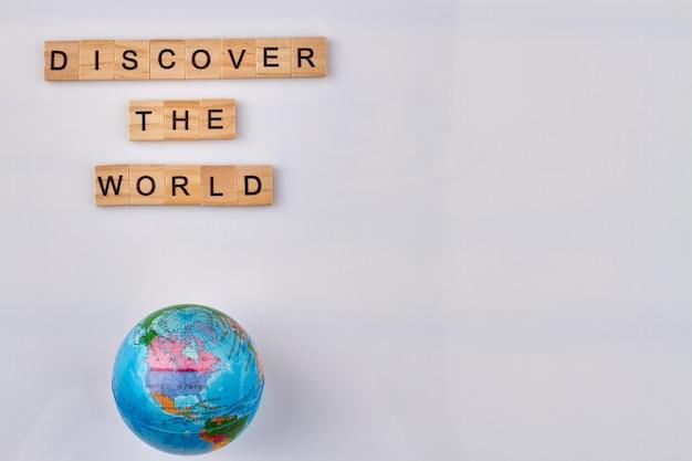 Reis- en avonturenconcept. ontdek de wereld. houten brievenblokjes op witte achtergrond.
