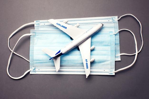 Reis- en gezondheidsconcept tijdens covid-19 pandemie. model van een wit plastic vliegtuig en maskers op grijze achtergrond.