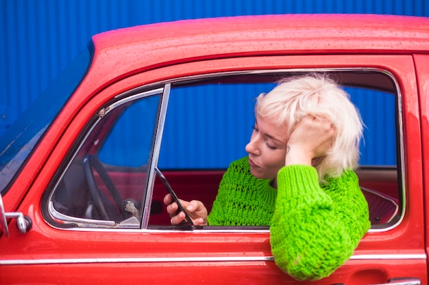 Reis- en modeconcept met aantrekkelijke mensen, een blanke dame in een rode retro mooie auto die via mobiele telefoon internet gebruikt om de kaart te controleren en nieuwe plaatsen te ontdekken. kleuren afbeelding.
