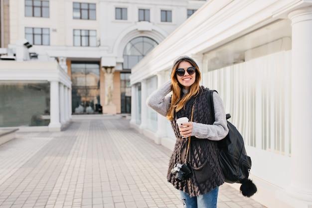 Reis gelukkige tijd in het moderne stadscentrum van een gezellige mooie jonge vrouw in zonnebril, warme winter wollen trui, gebreide muts. reizen met rugzak, koffie om mee te nemen, camera. plaats voor tekst.