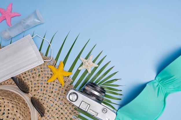 Reis in epidemische quarantaine-aantekeningen. tafelblad met camera, hoed, bikini, zonnebril, gezichtsmasker. artikelen voor persoonlijke hygiëne en bescherming in het thema toerisme. beperkingen