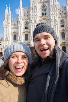 Reis, italië en grappig paarconcept - gelukkige toeristen die een zelfportret met duiven nemen voor duomo-kathedraal, milaan