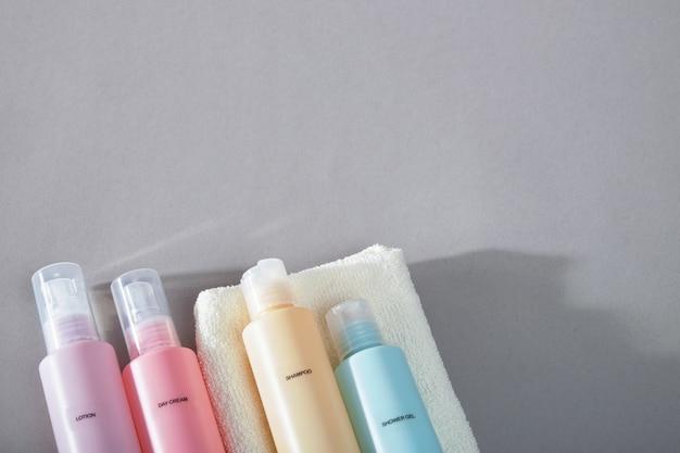 Reis kit. set van vier kleine plastic flesjes voor cosmetische producten, handdoek.