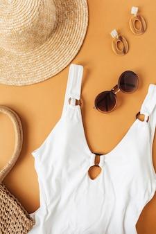 Reis mode collage met vrouwelijke kleding en accessoires op gember. badpak, strohoed, rotan tas, zonnebril, oorbellen