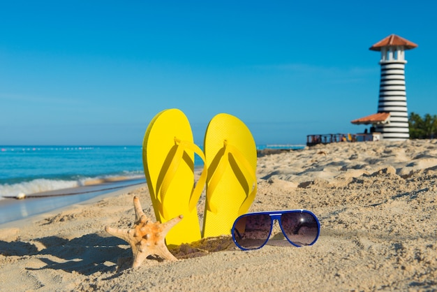 Reis naar de zee. zonnige positieve strandvakantie. gele sandalen, zonnebril, zeester en vuurtoren