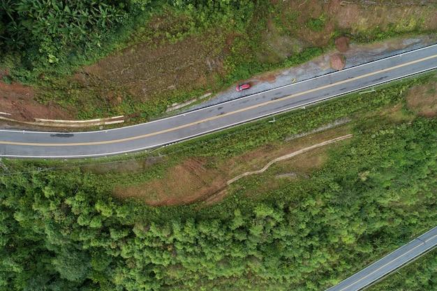 Reis op heuvelachtige weg in het voorjaar luchtfoto wegcurve constructie tot aan de berg verbazingwekkend top-down beeld van drone camera. Premium Foto
