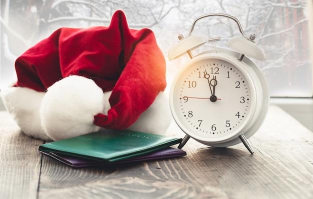 Reis op kerstmisconcept. vintage wekker met kerstman hoed en paspoort op houten tafel tegen het raam