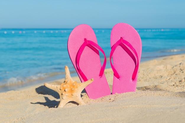 Reis over zee. strand vakantie. roze slippers en zeesterren aan zandige kust.