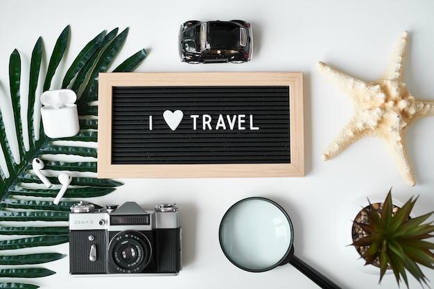 Reis plat. camera, beschermend masker, koptelefoon, bord met inscriptie i love travel op wit