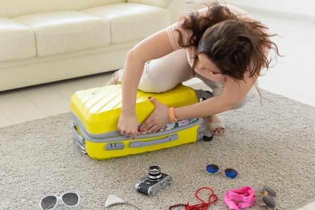 Reis-, reis- en vakantieconcept - vrouw die haar koffer probeert te sluiten