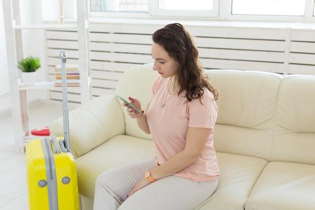 Reis-, reis- en vakantiesconcept - vrouw met gele koffer wacht op de taxi