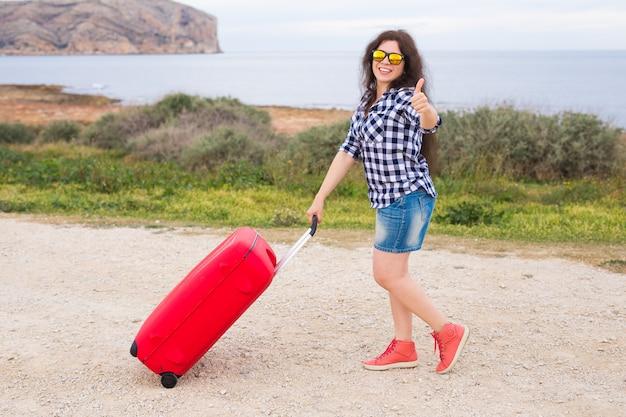 Reis-, toerisme- en mensenconcept - gelukkig meisje met een enorme koffer verschijnt duimen.