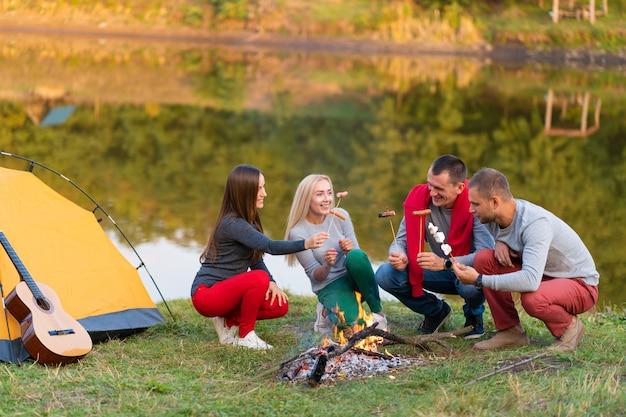 Reis, toerisme, stijging, picknick en mensenconcept - groep gelukkige vrienden die worsten op kampvuur dichtbij meer braden.