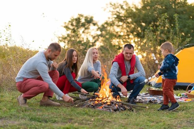 Reis, toerisme, stijging, picknick en mensenconcept - groep gelukkige vrienden met jonge geitjes die worsten op kampvuur braden.