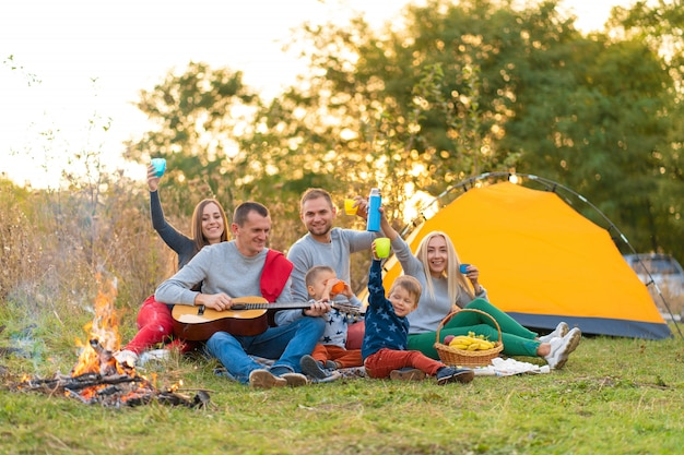 Reis, toerisme, stijging, picknick en mensenconcept - groep gelukkige vrienden met tent en dranken die gitaar spelen bij het kamperen