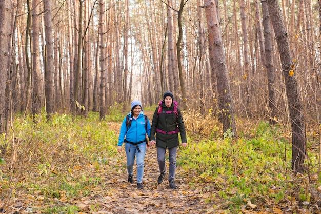 Reis-, toerisme-, wandeling- en mensenconcept - echtpaar met rugzakken wandelen in de herfst bos
