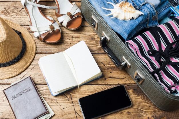 Reis voorbereidingen concept met koffer, kleding en accessoires op een oude houten tafel. bovenaanzicht ruimte kopiëren
