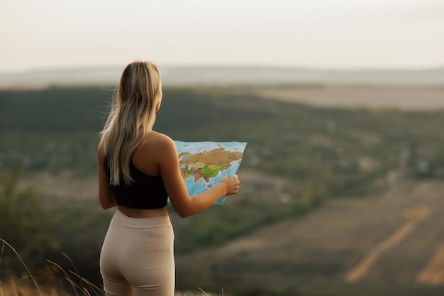 Reis vrouw leeskaart en geniet van het natuurlandschap. ze houdt een toeristische kaart vast en plant een route in de bergen.