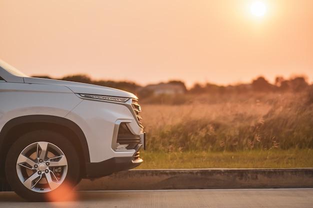 Reis witte auto die op de achtergrond van de wegzonsondergang wordt geparkeerd