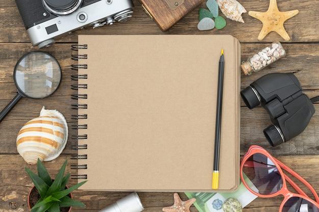 Reis zomersamenstelling met een notitieblok en potlood in het midden en reisaccessoires in de buurt