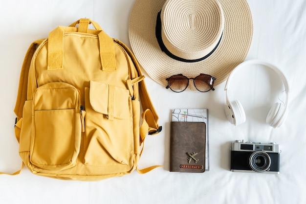 Reisaccessoires met strandhoed, zonnebril, rugzak, camera, koptelefoon en paspoort op bed thuis. bereid je voor op reis-, ontspannings-, reis-, reis- en vakantieconcepten. bovenaanzicht