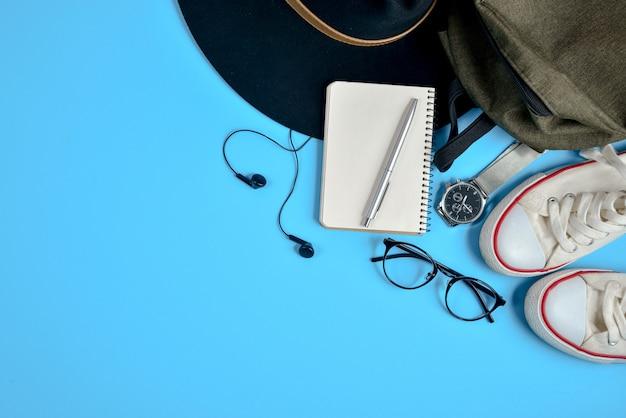 Reisaccessoires op blauwe achtergrond met hoed, rugzak, oogglazen, schoenen en blocnote.