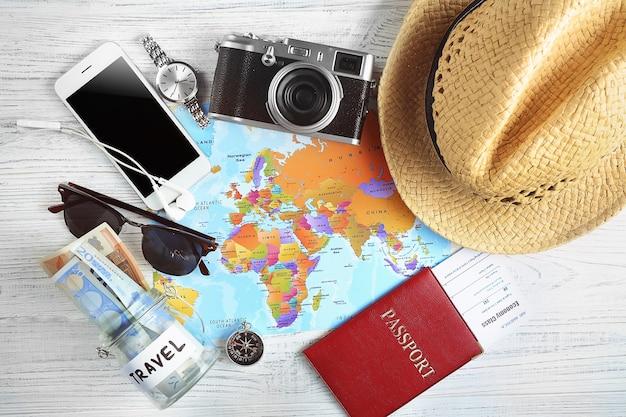 Reisaccessoires op wereldkaart, bovenaanzicht. reisplanning concept