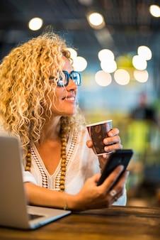Reisbaan en slim werkconcept levensstijl met jonge volwassen mooie vrouw gebruik telefoon en laptop met roaming-verbinding en gratis wifi luchthaven gate bar café Premium Foto