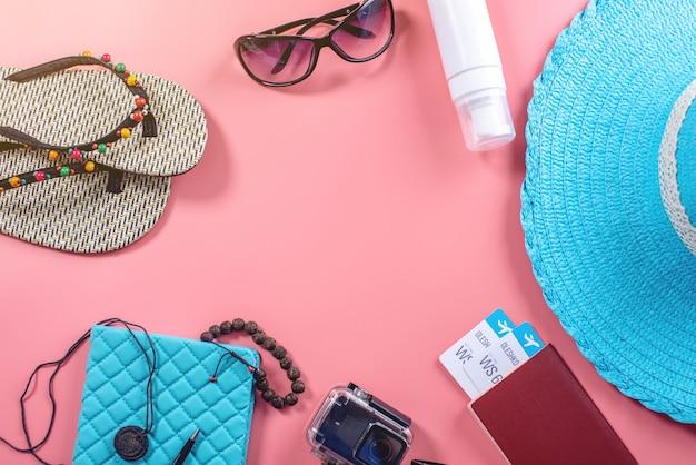 Reisbenodigdheden voor vakanties: hoed, zonnebril, camerapaspoort en vliegtickets op roze achtergrond