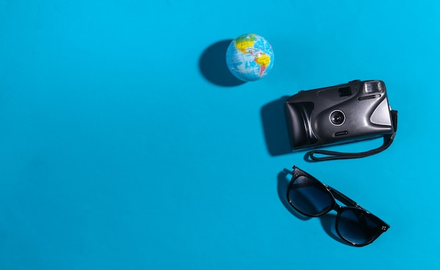 Reisconcept. camera en globe, zonnebril op blauwe achtergrond met schaduw. bovenaanzicht