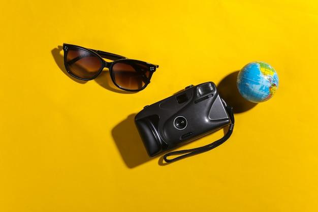 Reisconcept. camera, globe, zonnebril op gele achtergrond met schaduw. bovenaanzicht