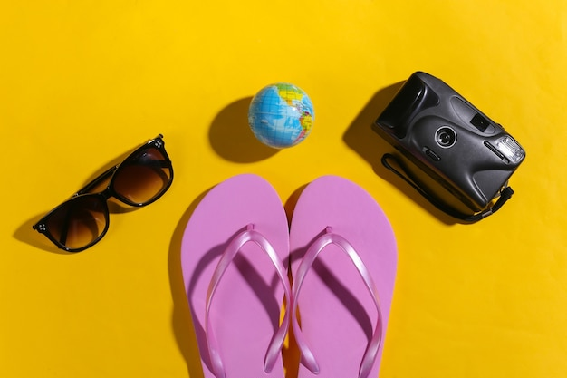 Reisconcept. camera, globe, zonnebril, slippers op gele achtergrond met schaduw. bovenaanzicht
